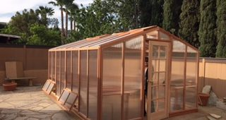 Deluxe redwood and polycarbonate greenhouse kit on backyard patio.