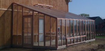 Large lean-to greenhouse kit made with glass and redwood.