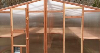Backyard greenhouse kit with redwood framing and polycarbonate siding.