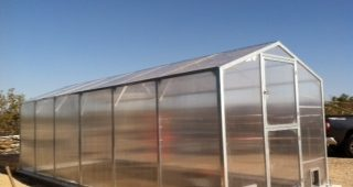 Large polycarbonate greenhouse kit with aluminum framing.