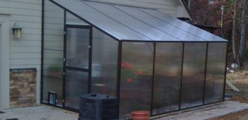 Aluminum lean-to greenhouse kit with polycarbonate paneling and flowers inside.