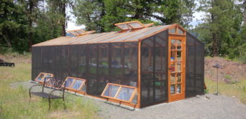 Backyard DIY greenhouse kit with a redwood frame, polycarbonate paneling and shade cloth.
