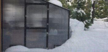 Aluminum and polycarbonate lean-to greenhouse kit in the snow.
