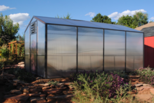 Backyard greenhouse kit with polycarbonate paneling and aluminum frame.