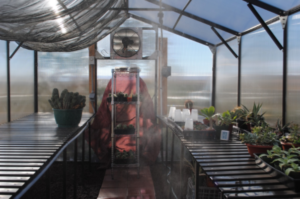 Aluminum greenhouse kit with fan and climate controls.