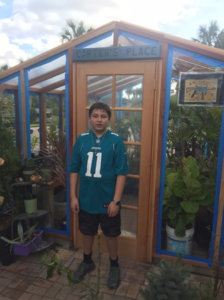 Our customer's son standing in front of his assembled backyard redwood greenhouse kit.