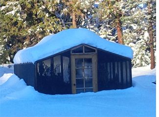 Redwood greenhouse kit in the snow.
